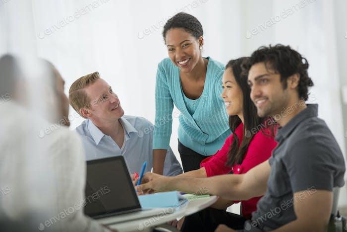 Ein Büro in der Stadt. Eine multiethnische Gruppe von Menschen um einen Tisch, Teamwork. Treffen.