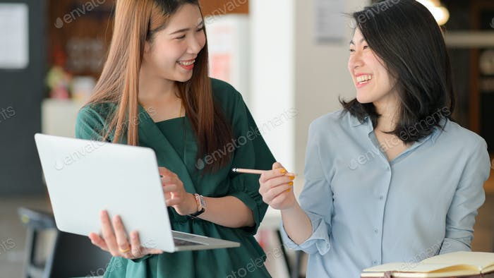 Young businesswomen use laptop to discuss the project together in modern office with good emotions.