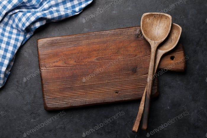 Kitchen table with utensils, cutting board and tablecloth