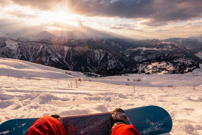 snowboarder with snowboard is sitting on the mountain on the sunset