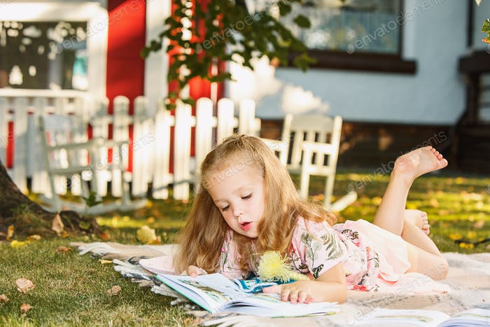 Cute Little Blond Girl Reading Book Outside on Grass