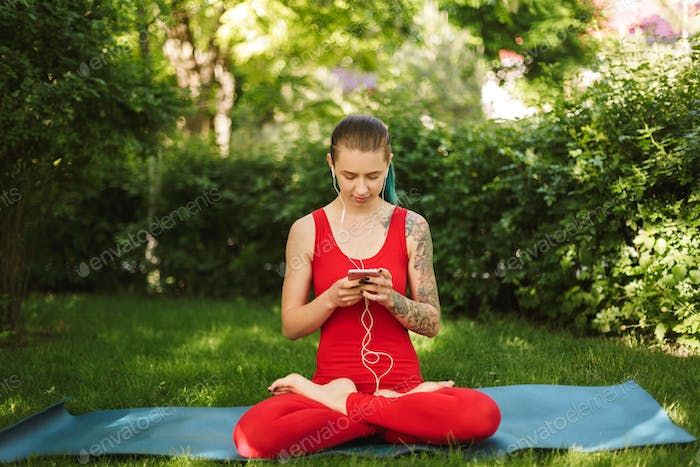 Beautiful woman in red jumpsuit sitting in lotus pose on yoga mat in park