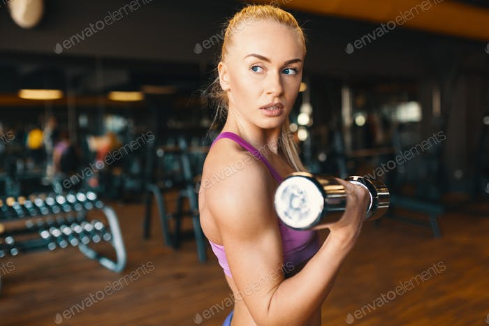 Young woman in pink top  doing exercise with dumbbells while tra