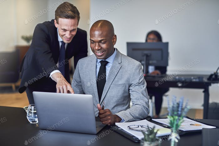 Two businessmen looking at something on a laptop at work
