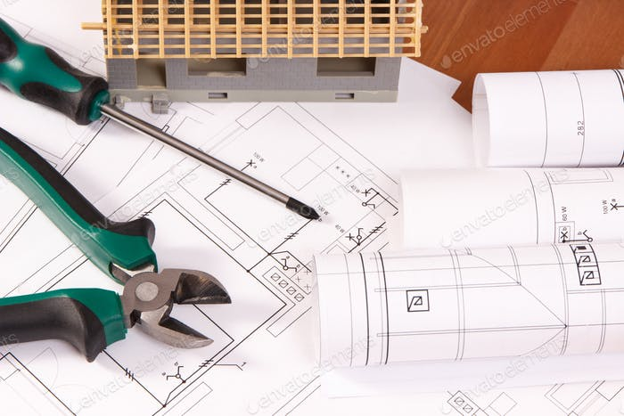 Electrical drawings, work tools and house under construction lying on desk, building home concept