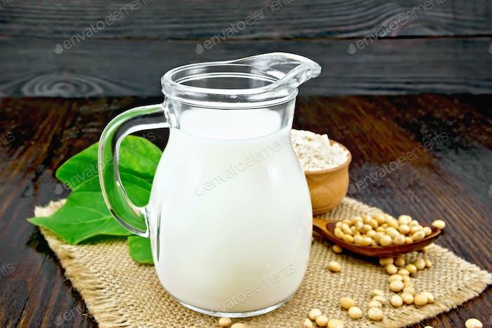Milch Soja in Krug mit Mehl auf dunklem Brett