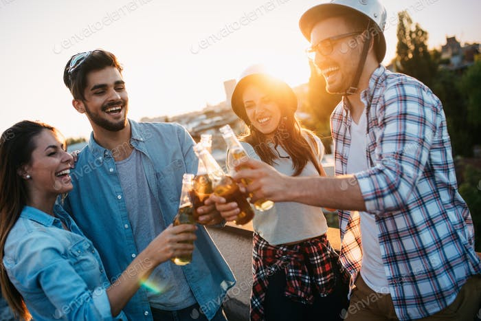 Young friends hanging out with drinks on rooftop