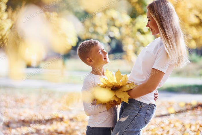 Mother with son have a rest in an beautiful autumn park at sunny day
