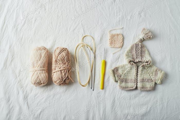 Handgefertigte gestrickte kleine Pullover und Fäden auf hellem Hintergrund.