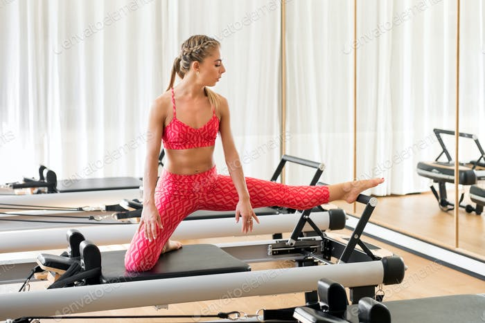 Woman doing leg stretching exercises in a gym