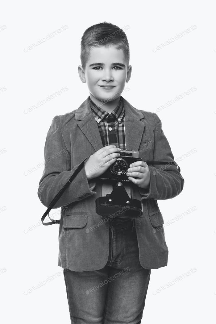 Handsome young boy with retro camera