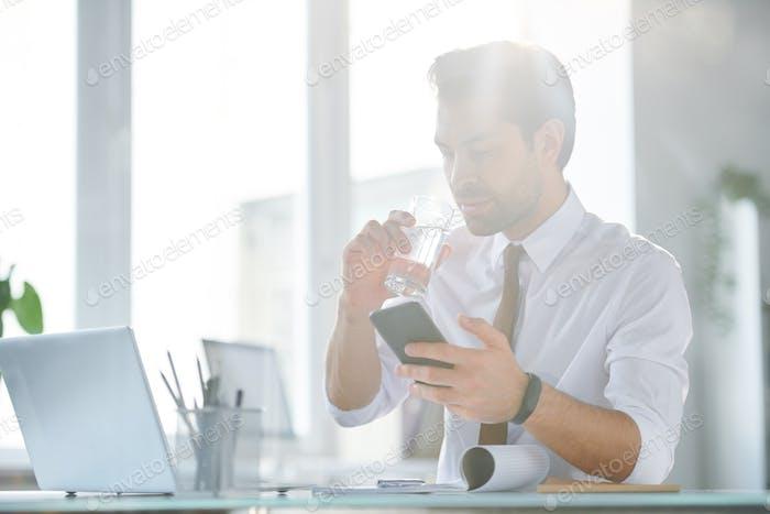 Hübscher junger Geschäftsmann mit mobilen Gadget Trinkwasser