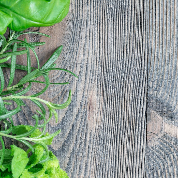 Basil, mint, rosemary. Fresh green herbs laying on wooden backgr
