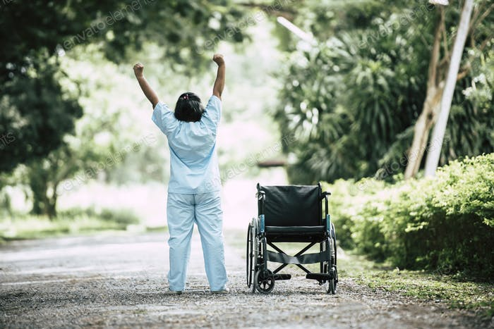 Physical therapy senior woman with wheelchair in the park