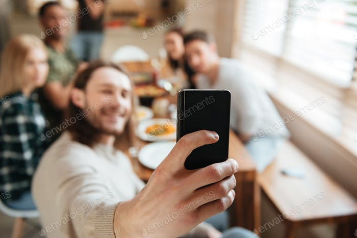 Man taking a selfie photo with friends in the kitchen