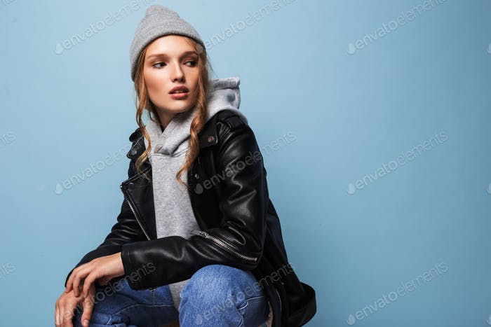 Beautiful teenager girl in hat and black leather jacket looking aside over blue background