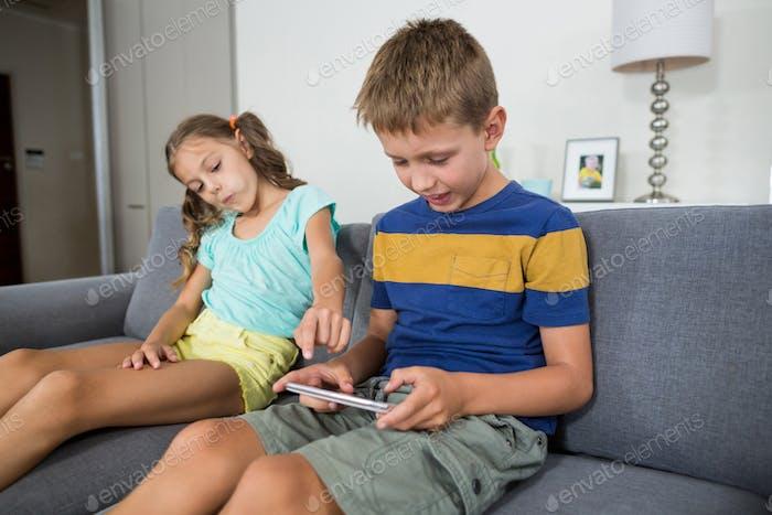 Smiling siblings using digital tablet on sofa in living room