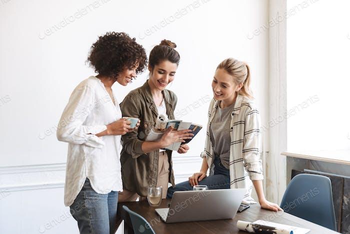 Gruppe von fröhlichen jungen Frauen, die zusammen studieren
