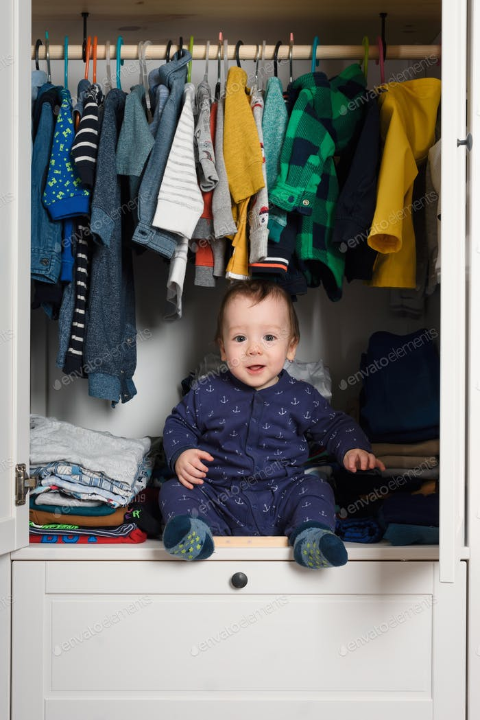 Smiling kid hiden in clothing closet