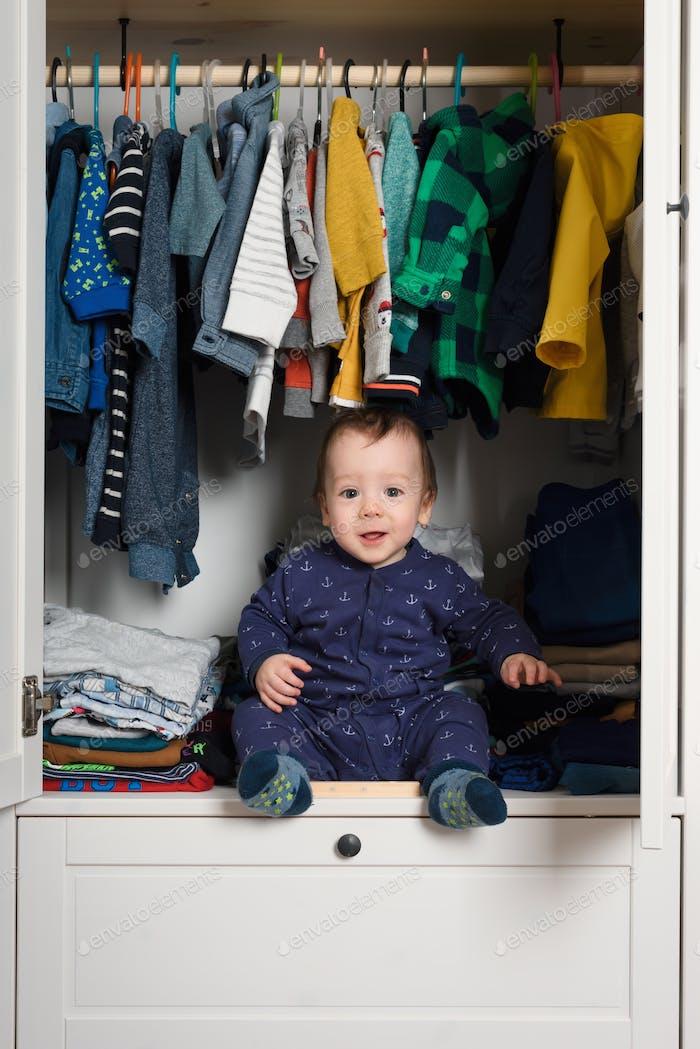 Lächelnd Kind versteckte sich in Kleidung Schrank