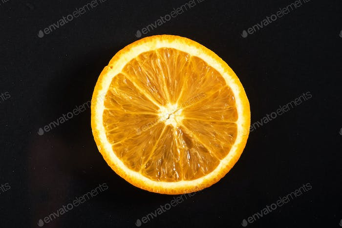 A piece of fresh orange, isolated on a black background.