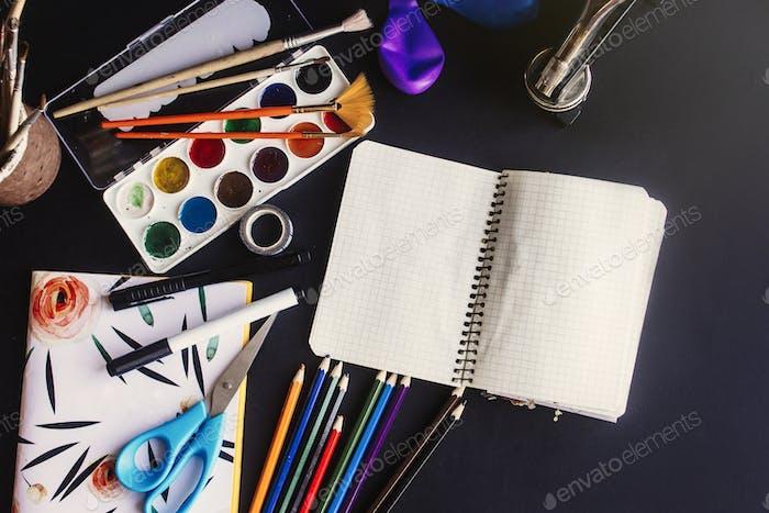 Bunte Bleistifte Farben Pinsel Schere und Notizbuch