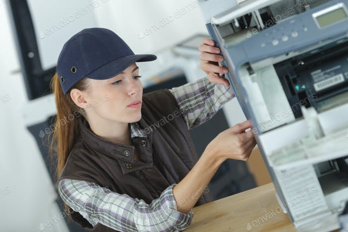 Woman servicing office photocopier