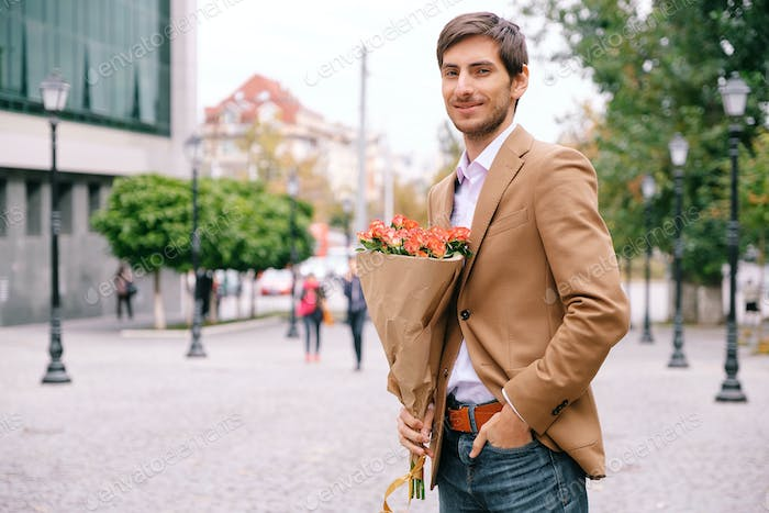 Portrait of young handsome man smiling holding a bunch of roses