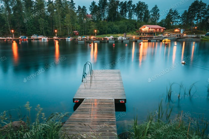 Sweden. Beautiful Wooden Pier Near Lake In Summer Evening Night.