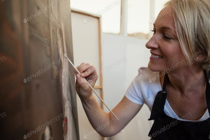 Happy woman painting on canvas