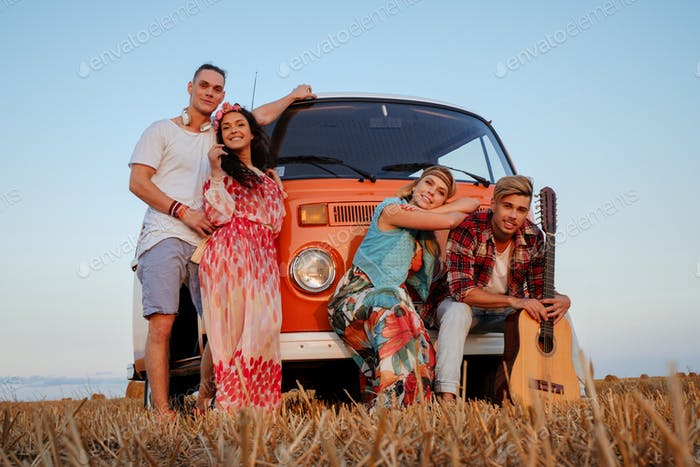 Hippie friends with guitar on a road trip
