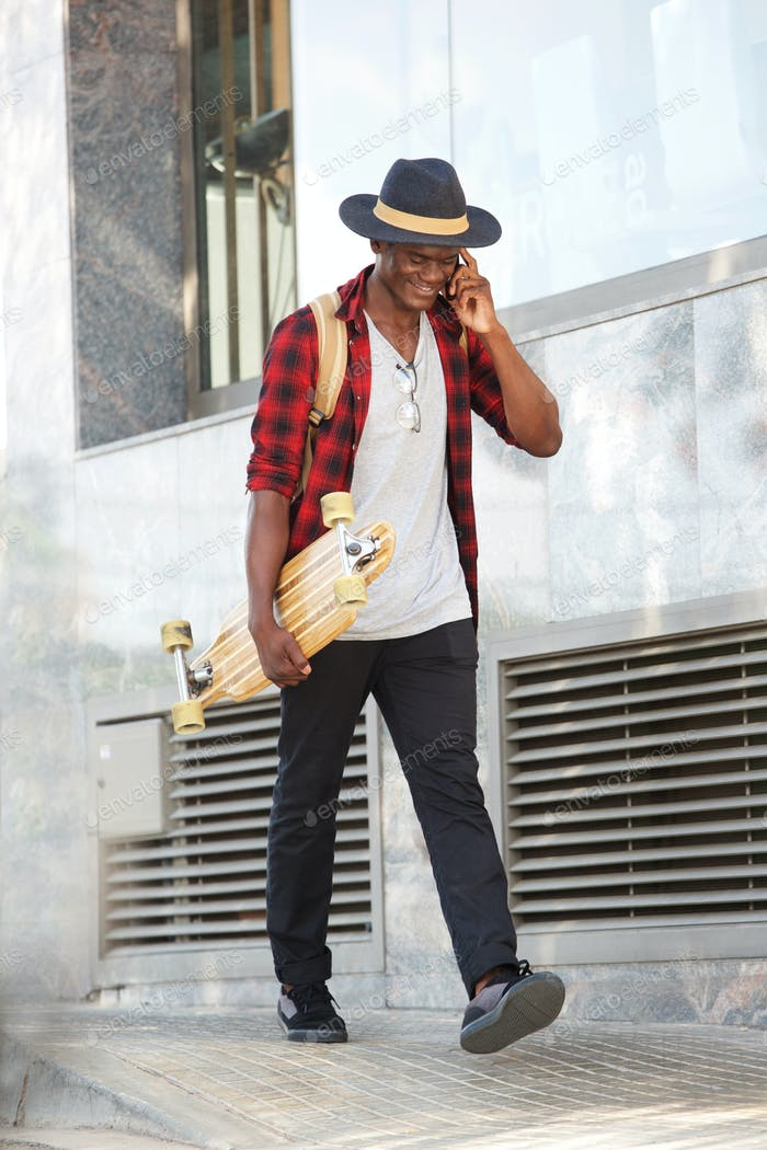 Full body smiling african man with skateboard talking on cell phone