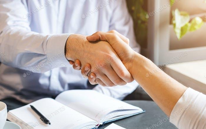 Handshake of two businessmen during lunch break