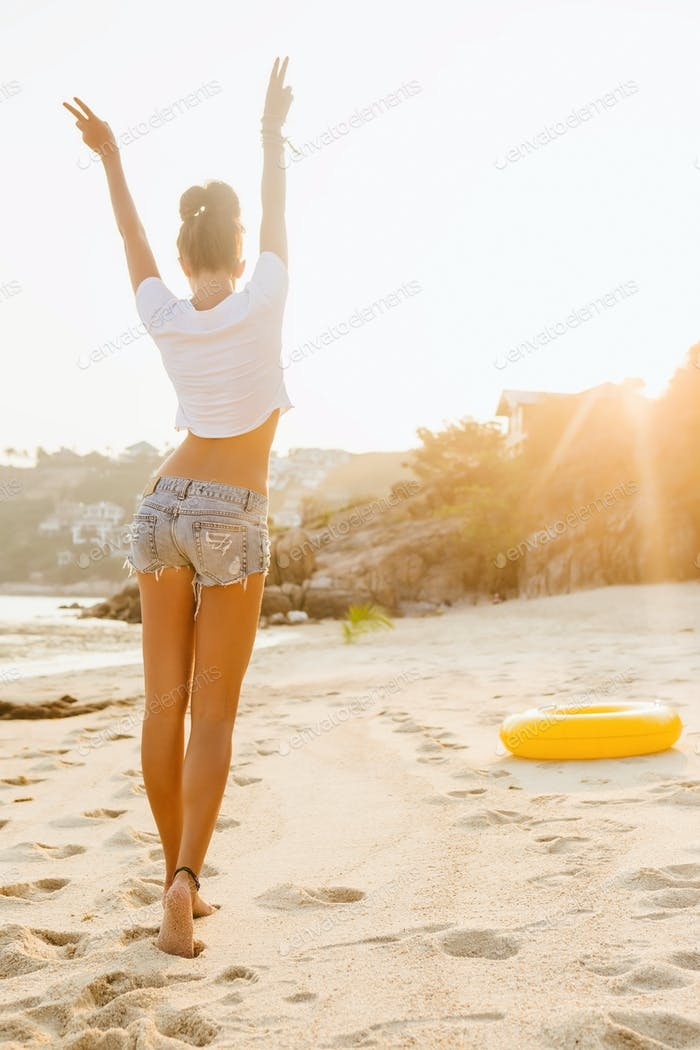 Girl in shorts walk on the beach.