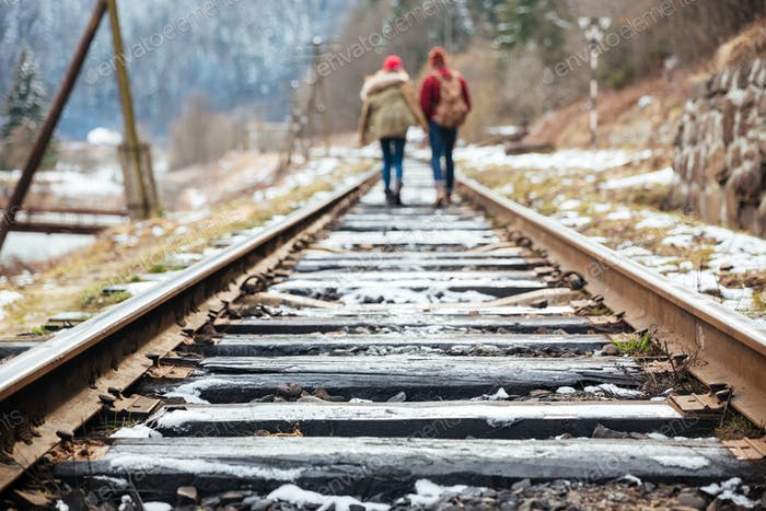 Couple walking far away on railroad together