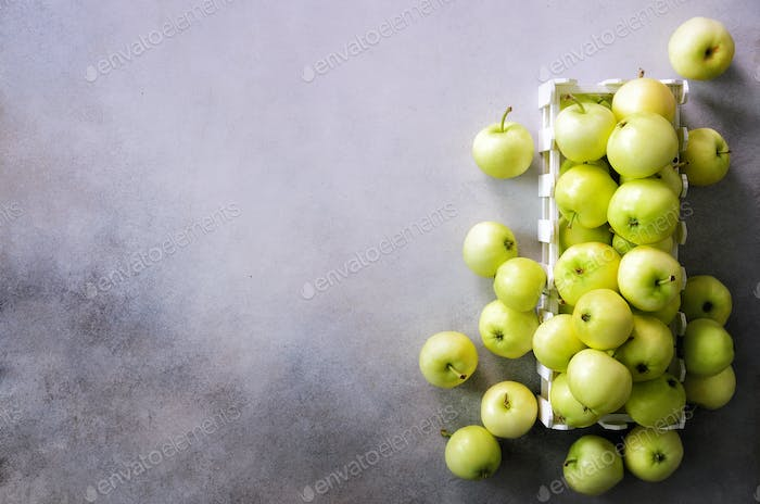 Fresh green apples in wooden box on light grey background. Free space for text. Copy space. Top view