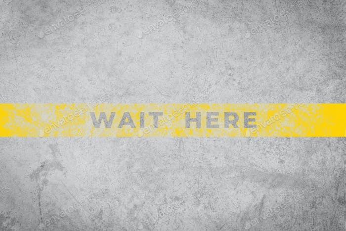 Wait Here sign on aged concrete floor