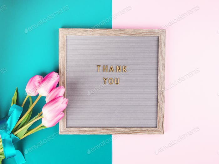 Thank you written on board with bunch of flowers