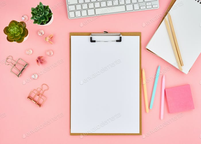 Blank notepad page for text on pink office desktop. Top view of modern bright table with notebook