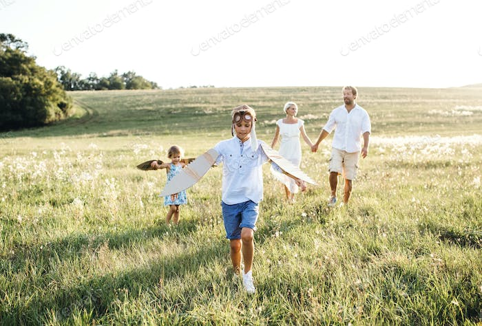 Young family with small children playing on a meadow in nature.