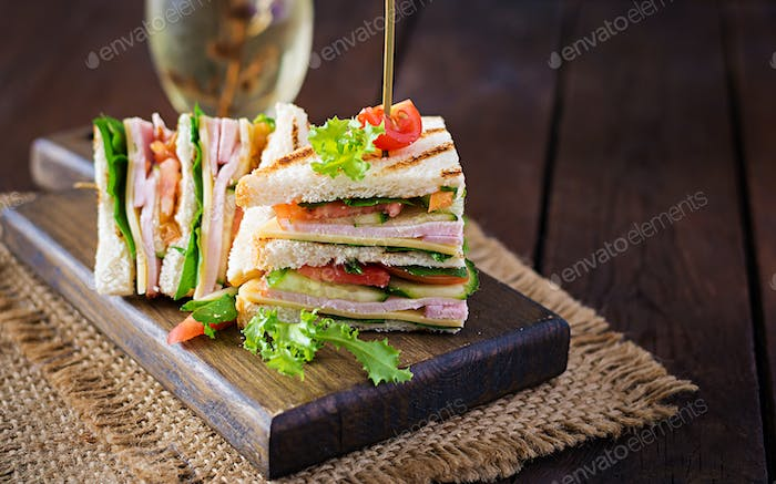Club sandwich with ham, tomato, cucumber, cheese,  and arugula on wooden background.