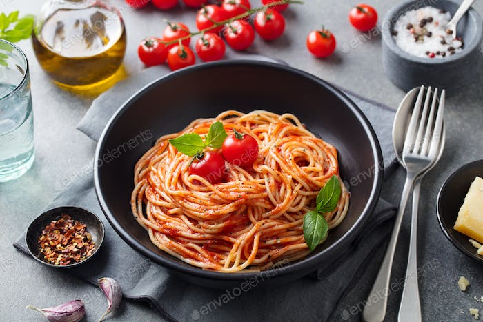 Pasta, Spaghetti with Tomato Sauce in Black Bowl on Grey Background. Traditional Italian Cuisine.