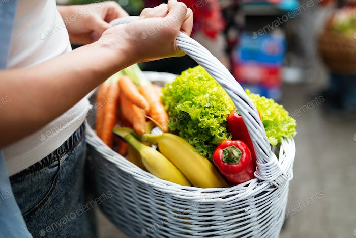 Woman holding a basket with healthy organic vegetables