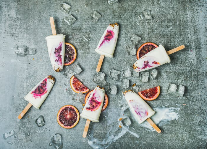 Blood orange, yogurt and granola popsicles on ice, concrete background