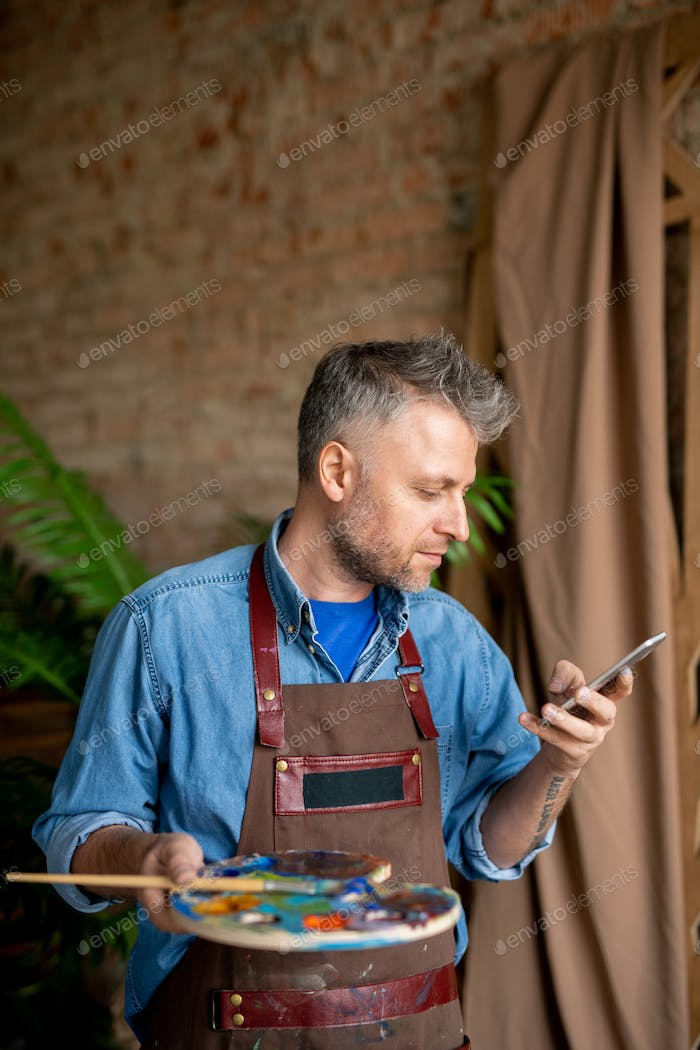 Serious artist in workwear looking at smartphone screen while texting