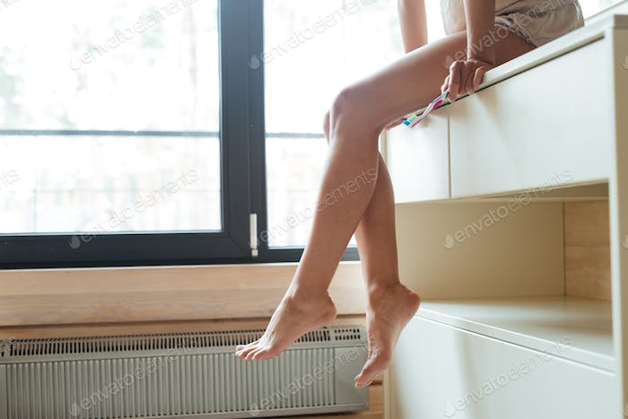 Beautiful barefoot legs of slim young woman sitting in bathroom