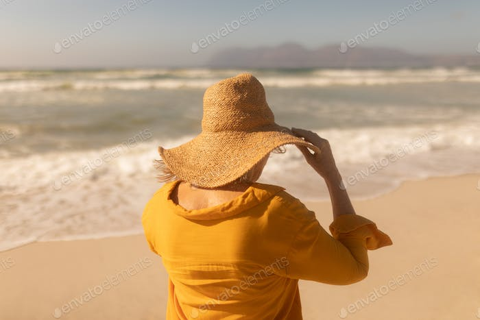 Rear view of active senior woman in hat standing on the beach