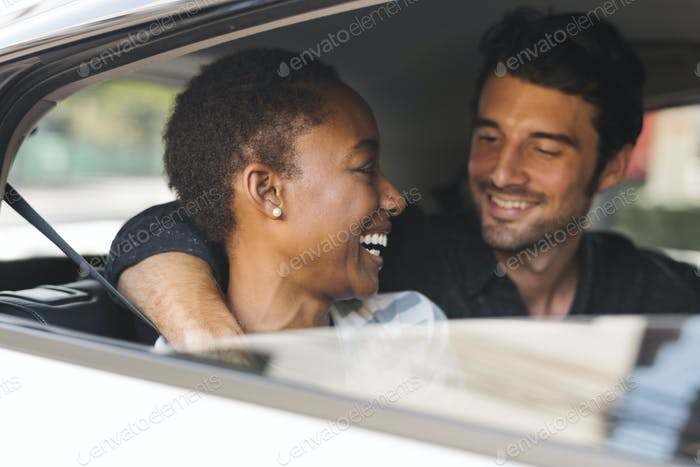 Glückliches Paar, das über ein Auto transportiert