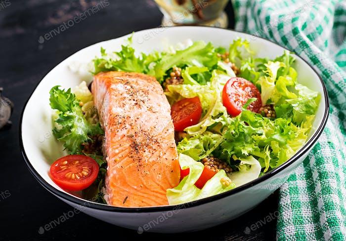 Baked salmon fillet with fresh vegetables salad.