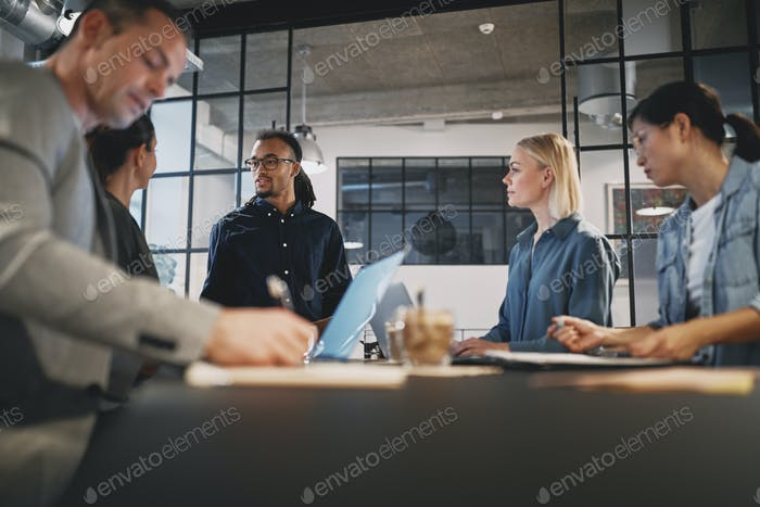 Young businessman talking with staff during an office meeting